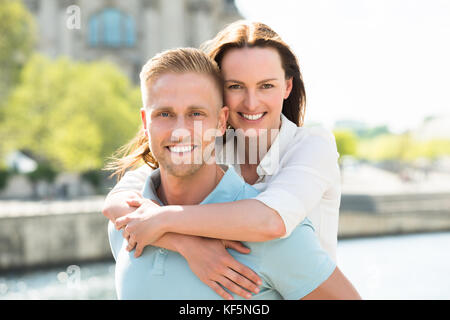 Portrait Of Young Happy Man Carrying Woman On His Back - Stock Photo