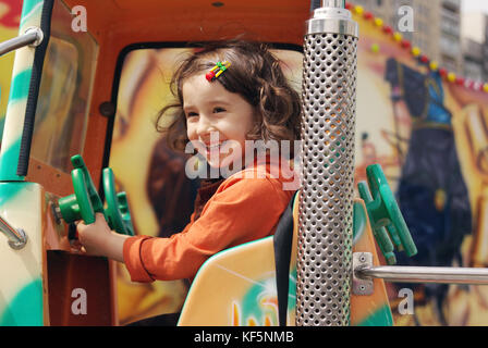 Cute little girl ride on a children's train and smiles happily - Stock Photo