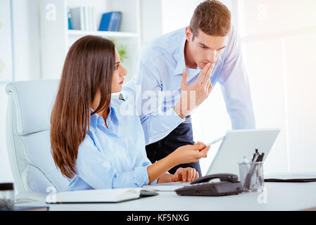 Two young business people talking in the office. Woman sitting at an office desk, behind her standing a young man - Stock Photo