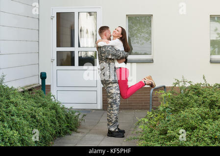 Young Happy Wife Welcoming Her Husband From Army Leave - Stock Photo