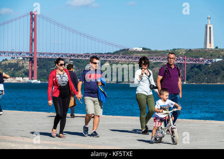 Lisbon Portugal Belem waterfront promenade Tagus River Ponte 25 de Abril 25th of April Bridge suspension tower view - Stock Photo