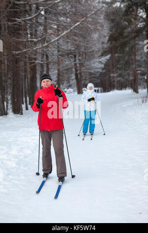Father and daughter stay together on snow skiing run in wintry forest - Stock Photo