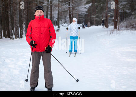 Senior father with adult daughter skiing on cross-country skis in winter forest - Stock Photo