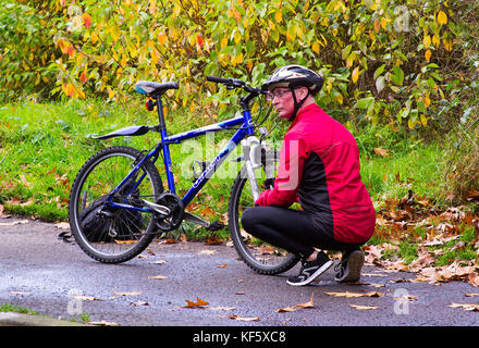 An ageing cyclist in full cycling gear makes some running repairs to his bicycle on a damp day in autumn - Stock Photo