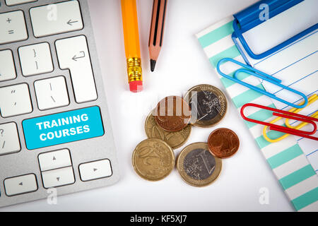 Training Courses concept. Computer keyboard on a white office desk with various items - Stock Photo