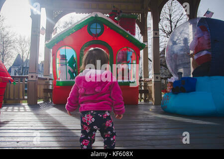 Toddler walking toward Christmas or holiday displays. - Stock Photo