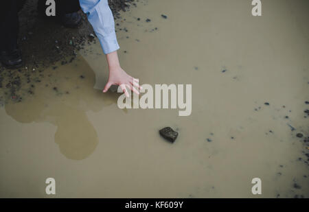 A boy reaching for a rock in a mud puddle. - Stock Photo