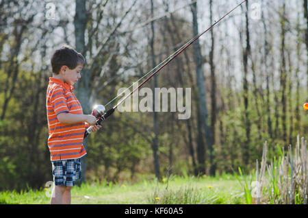 5-6 year old boy fishing by a pond in summer. - Stock Photo