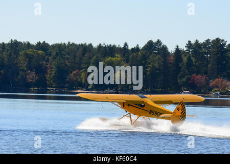 Bright yellow 2005 Cub Crafters float plane taking off on Lake Pleasant in the Adirondack Park. - Stock Photo