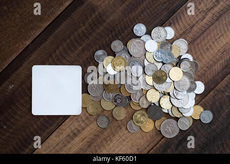 saving concept - coins in a jar with white empty note on a wooden table / background