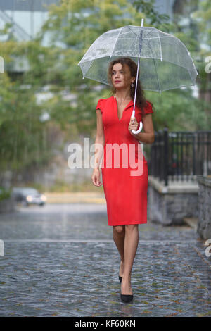 Woman in red elegant dress walking with an umbrella in the rain on a city street - Stock Photo