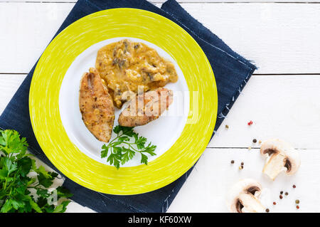 Roasted carp steaks with mushroom sauce on a plate on a white wooden background. Top view. Dish from the river fish. - Stock Photo