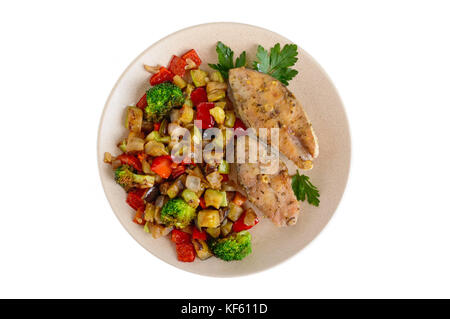 Steaks of fried spicy fish, served with a warm vegetable salad on a ceramic plate. Isolated on white background. - Stock Photo