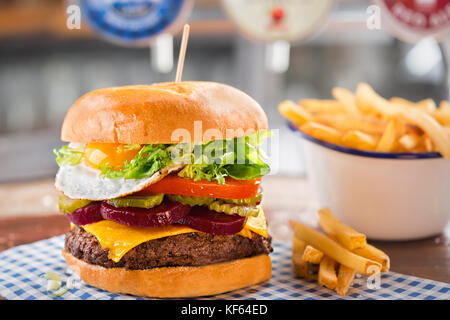 Beef burger with cheese, lettuce, tomato, beetroot & pickle, topped with a fried egg - Stock Photo