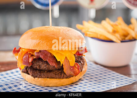 Double beef burger with cheese and bacon, bowl of fries - Stock Photo
