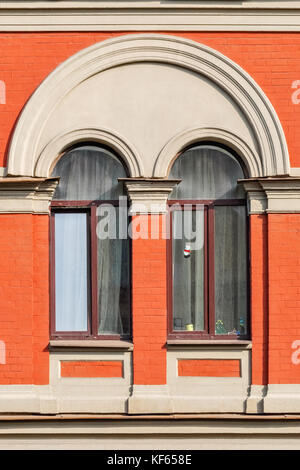 Two windows with white arches in the background of wall of red brick. From the window of Saint Petersburg. - Stock Photo