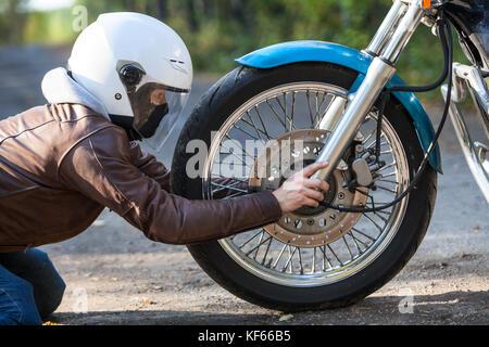 Woman in white helmet sitting on the kneels on the ground against motorbike spoked wheel, holding axis, repairing works