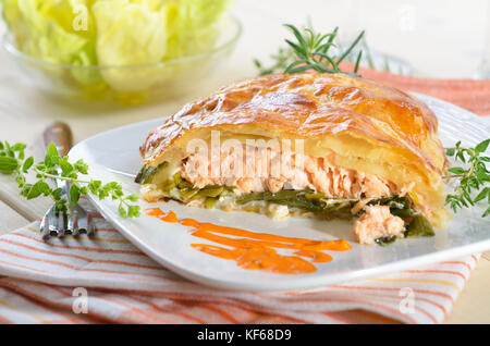 Salmon fillet on leek, baked in puff pastry, served with herbs, sauce and side salad - Stock Photo