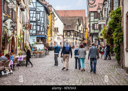 Tourists and pedestrians on the cobbled Rue du Général de Gaulle in Riquewihr, Alsace, France. Shops and cafes. - Stock Photo
