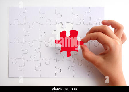 Young girl hand placing the last puzzle piece of a Jigsaw puzzle. Problem solving concept. Copy space - Stock Photo