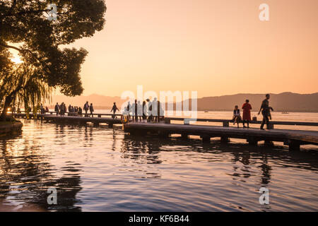 Happy people enjoying the calmness of west lake hangzhou, walking on an elevated walkway above the lake. Mountains - Stock Photo