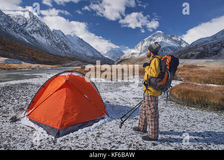 Hiker with backpack at camping in the mountains during springtime. - Stock Photo