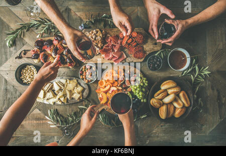 Top view of people drinking and eating together over table - Stock Photo
