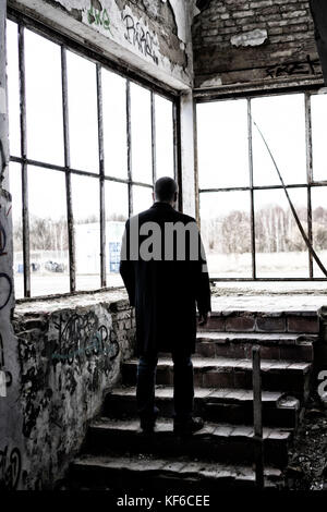 Rear view of a mysterious male figure standing on the steps inside a derelict building - Stock Photo