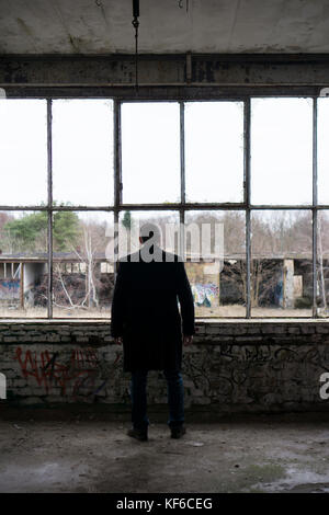 Rear view of a man wearing a coat standing by broken windows insisde a derelict building - Stock Photo