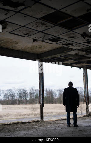 Rear view of a man wearing a coat standing inside a derelict building - Stock Photo
