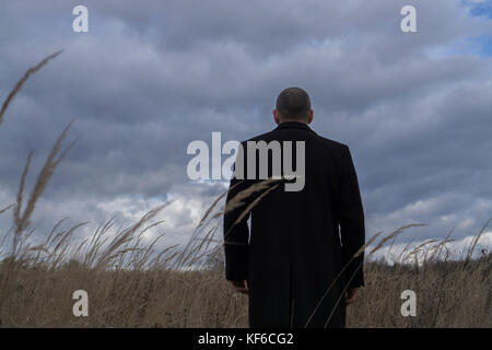 Rear view of a man wearing a coat standing in a field with cloudy sky - Stock Photo