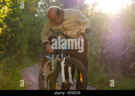 Senior caucasian man on cycle ride in countryside. Cycle is broken and he is looking why - Stock Photo