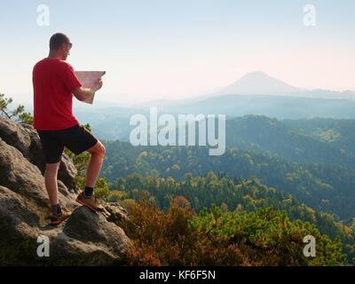 Lost tourist  on the rocky peak looking into landscape  while check the paper  map, hiking  in nature. Autumnal - Stock Photo
