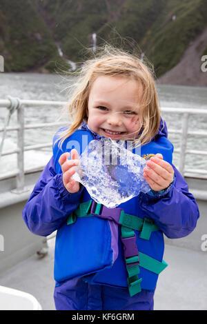 USA, Alaska, Seward, playing with chucks of glacial ice from Holgate Glacier seen while exploring Resurrection Bay - Stock Photo