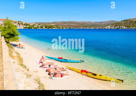 ROGOZNICA, CROATIA - SEP 4, 2017: tourists relaxing on beautiful beach and two colorful kayaks on shore in Rogoznica - Stock Photo