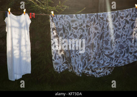 cotton bed sheets and linen, hang out on a laundry line outside in the garden - Stock Photo