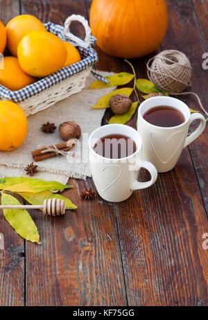 tea with lemon, honey, oranges, autumn leaves on woodenbackground - Stock Photo