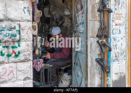 A cobbler working in his workshop. Madaba, Jordan - Stock Photo