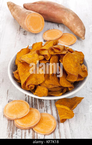 Fried and raw red batata chips on white wooden table. - Stock Photo