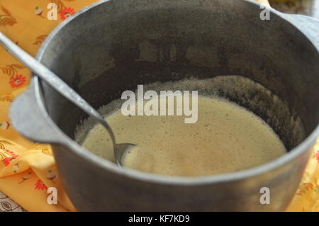 Mixed batter and a spoon in cast-iron bowl, close-up, selective focus. Process of cooking. - Stock Photo