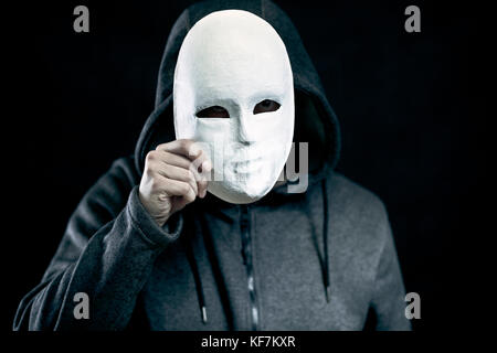 Man holding white mask for hide his face - Stock Photo