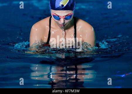 portrait of woman swimming with swimming hat and glasses in swimming pool - Stock Photo