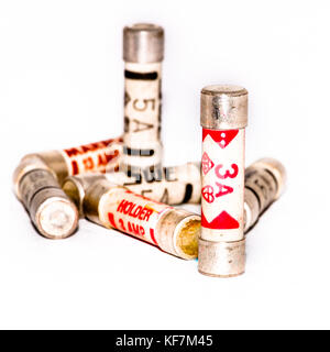 A small collection of three and five amp fuses shot against a white background. - Stock Photo