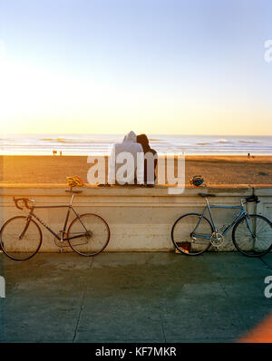 USA, San Francisco, a couple sit and watch the sunset at Ocean Beach - Stock Photo