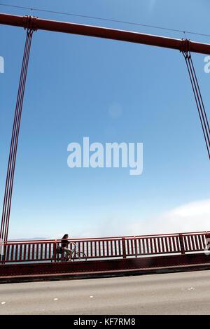 USA, California, San Francisco, a woman bikes across the Golden Gate Bridge on the East side of the bridge - Stock Photo