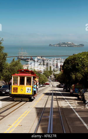 USA, California, San Francisco, a trolly drives up Hyde street with the San Francisco Bay and Alcatraz in the distance - Stock Photo