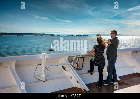 CANADA, Vancouver BC, a couple takes pictures off the Holland America cruise ship, the Oosterdam, as it leaves Vancouver - Stock Photo