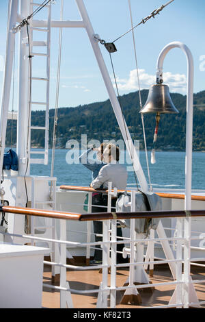 CANADA, Vancouver BC, a couple takes in the scenery off the Holland America cruise ship, the Oosterdam, as it leaves - Stock Photo