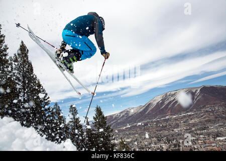 USA, Colorado, Aspen, skier getting air on a trail called Corkscrew with the town of Aspen in the distance, Aspen - Stock Photo
