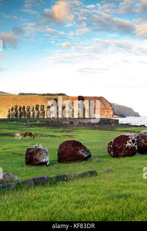 EASTER ISLAND, CHILE, Isla de Pascua, Rapa Nui, horses graze in front of the Moai statues at the Ahu Tongariki site - Stock Photo